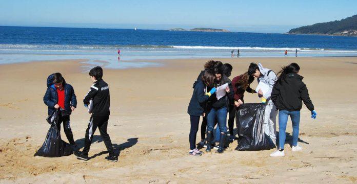 Jornada medioambiental de 57 alumnos del IES Val Miñor en los arenales de playa América y Panxón