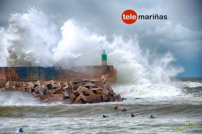 Un grupo de surfistas cabalgan en el puerto de A Guarda en pleno temporal