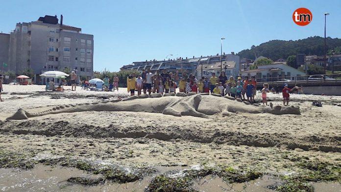 Niños del campamento urbano de Baíña realizan un dragón de arena en la playa de Santa Marta
